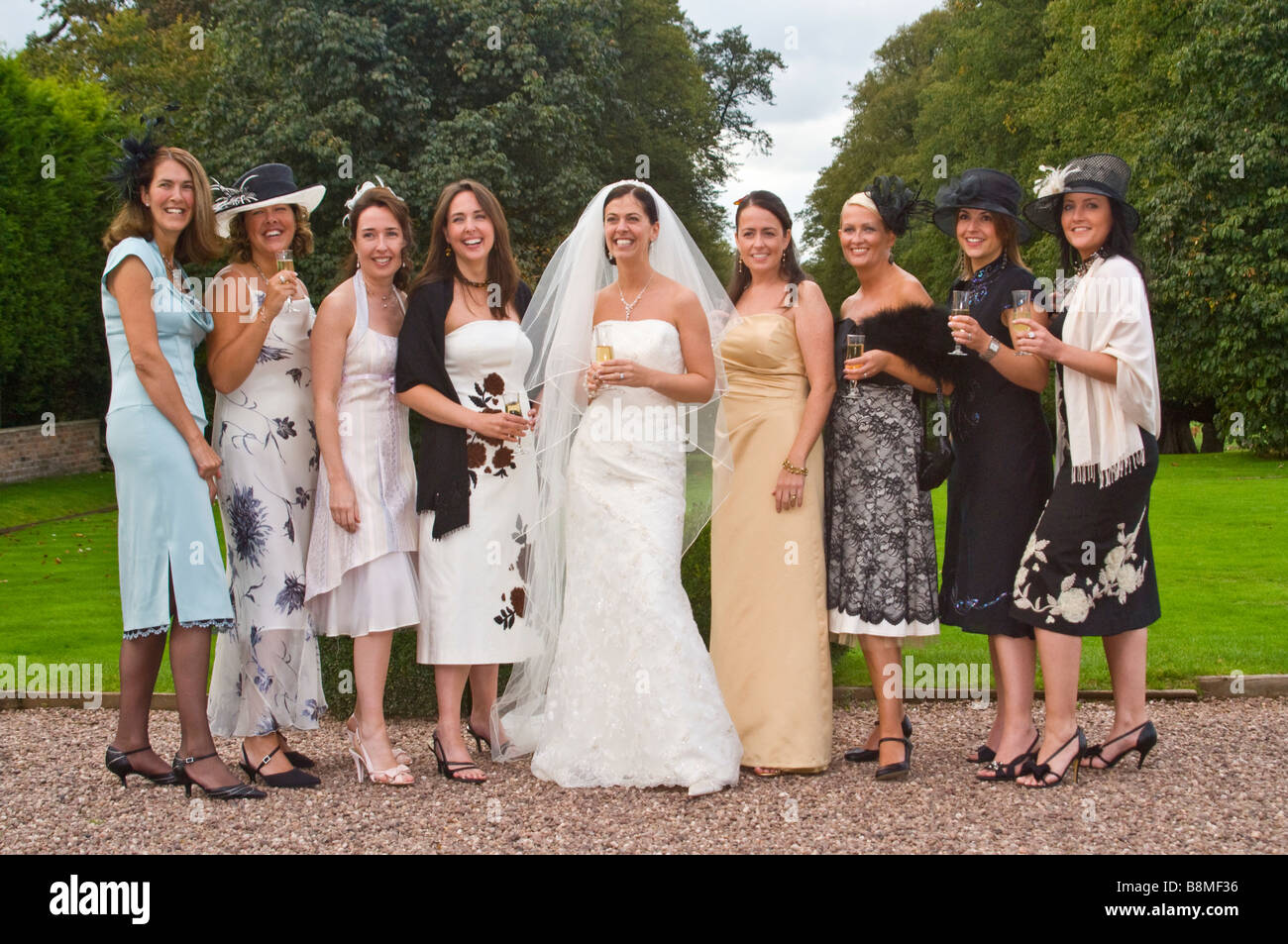 Horizontal informal group portrait of a traditional bride with all her female friends and family at a civil wedding - Stock Image