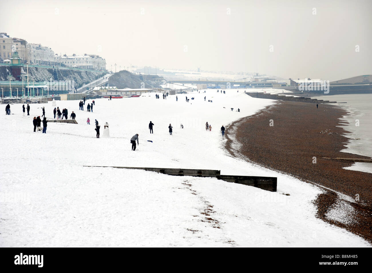 People make snowmen on Brighton beach after a heavy fall brings the city to a standstill and most people take a - Stock Image