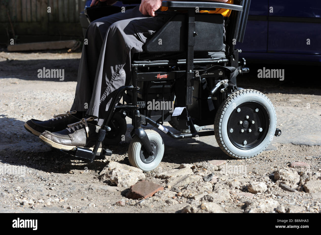 A disabled man in a motorised wheelchair gets stuck on some uneven ground - Stock Image