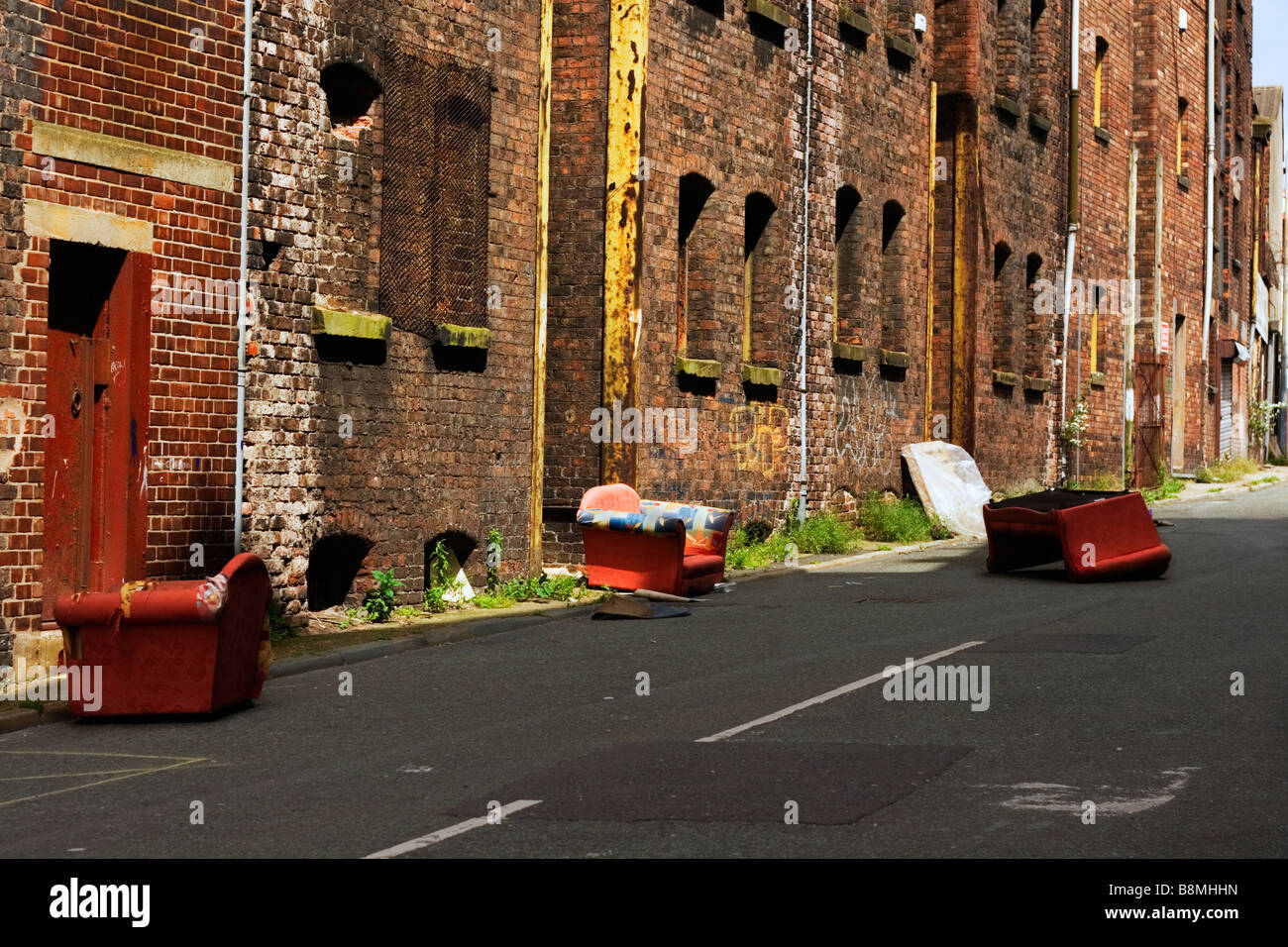 Example of the fly tipping problem, old settees dumped in a Liverpool street - Stock Image