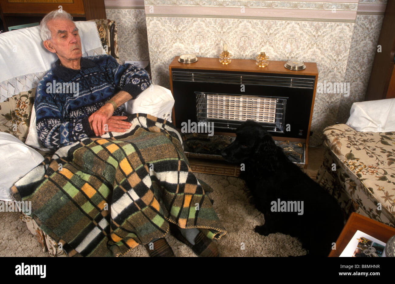 elderly man covered with a blanket to protect against the cold sitting in front of a fire with his dog - Stock Image