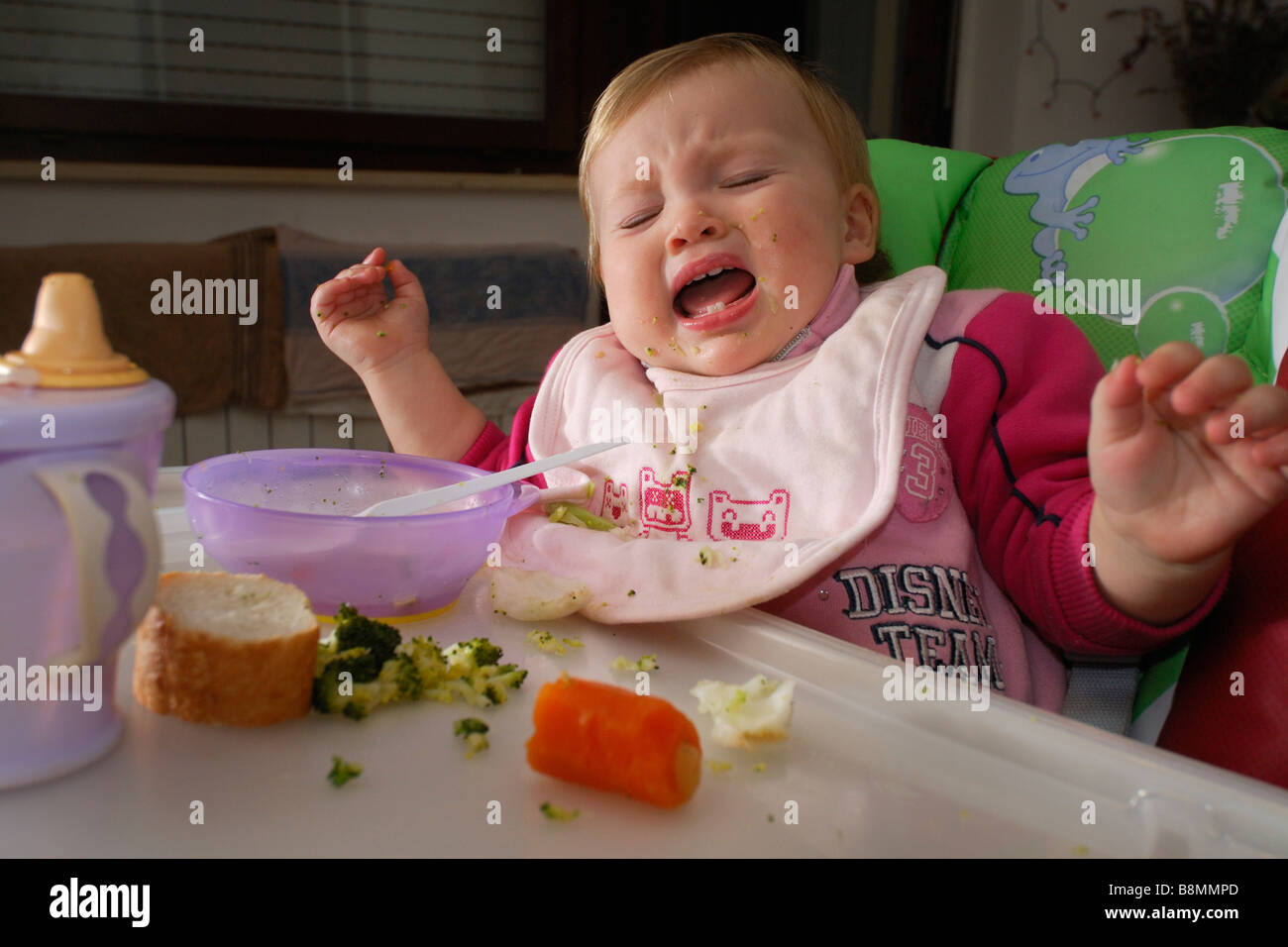 One year old baby girl crying in highchair at meal time - Stock Image