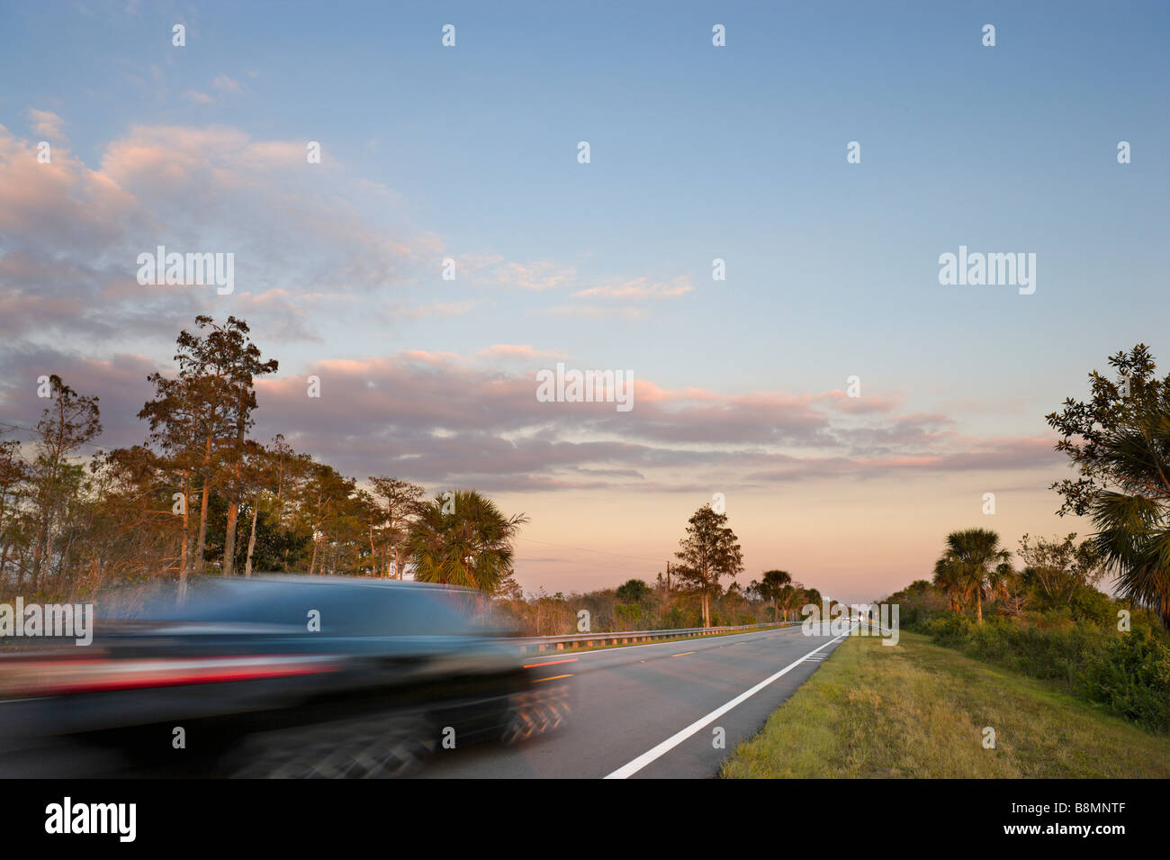 Everglades, Florida. Speeding car at sunset on Tamiami Trail (US 41) in Big Cypress National Preserve, Florida Everglades, - Stock Image