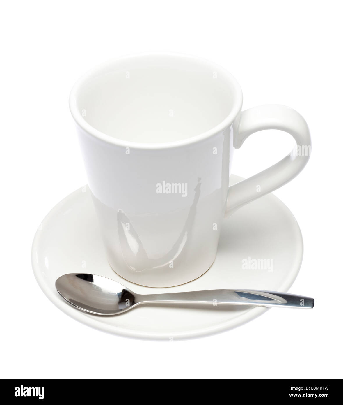 Empty white mug and saucer with spoon on white cutout - Stock Image