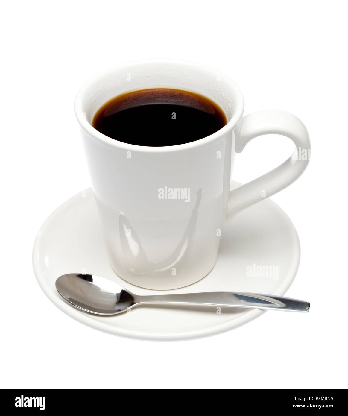 Cup of black coffee on saucer with spoon on white cutout - Stock Image