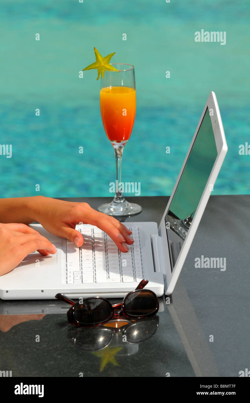 Laptop computer and cocktail by pool - Stock Image