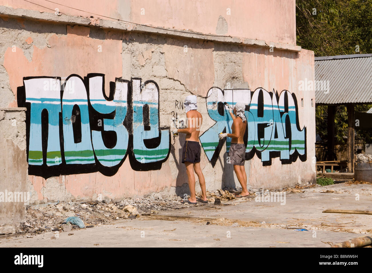 India Andaman and Nicobar Havelock island number 3 village bazaar Russian travellers painting grafitti on wall - Stock Image