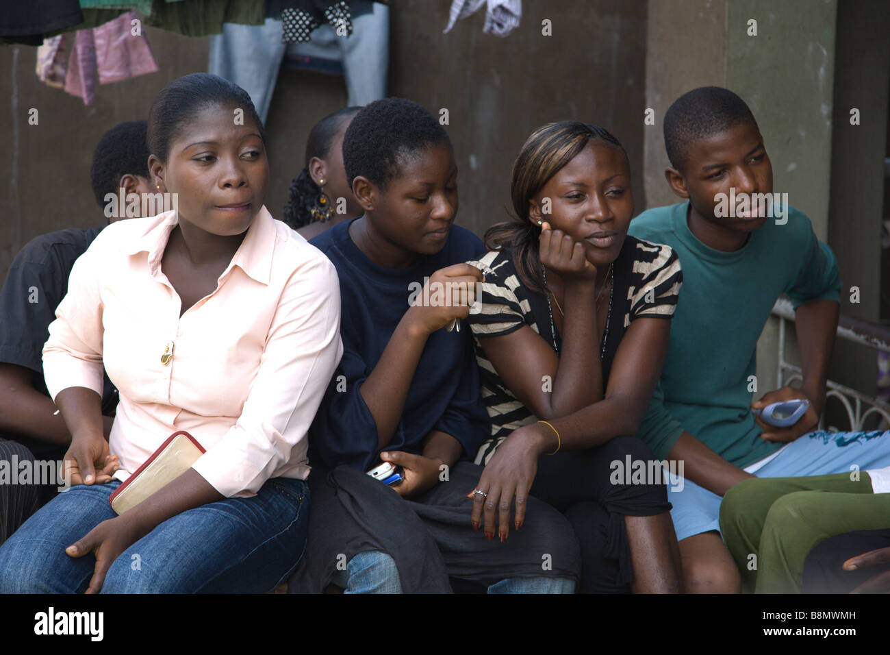 A group of young men and women in Lagos, Nigeria listen to one of their peers talk about how to prevent HIV/AIDS. - Stock Image
