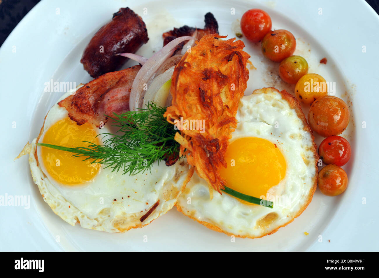Breakfast, plate of fried eggs, bacon sausage and tomato - Stock Image