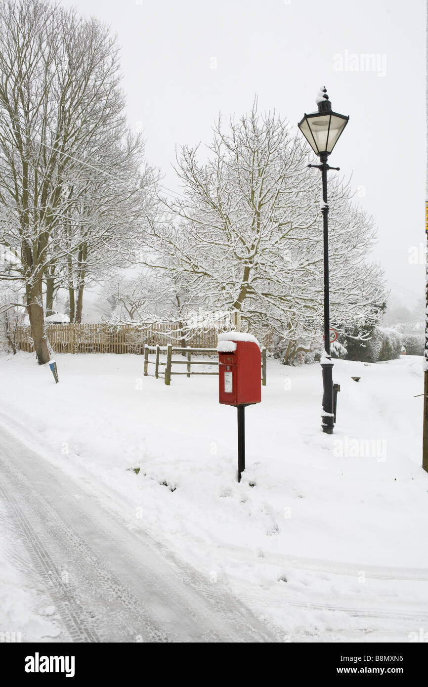 pictorial snow scene of a country village with red letterbox and lamp post - Stock Image