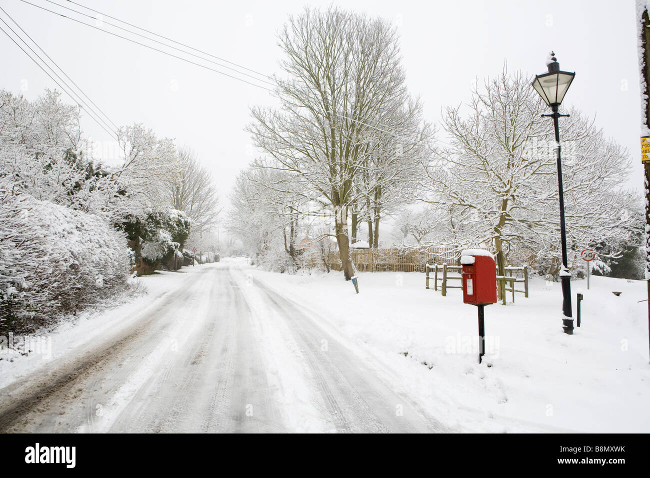 Royal Mail red post box and traditional style lamp post in the snow covered Buckinghamshire village of Askett. - Stock Image