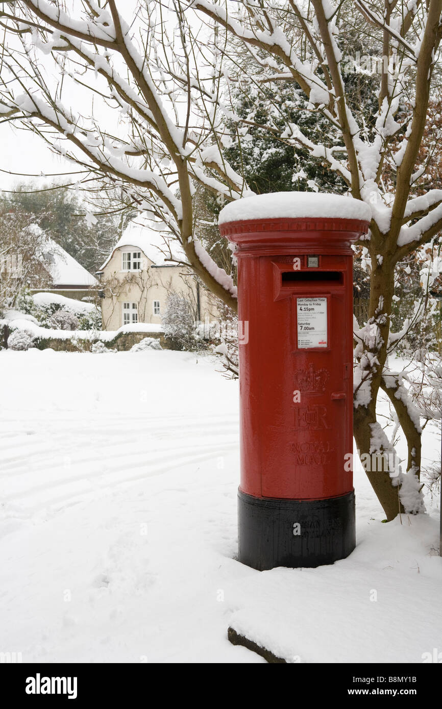Royal Mail red mail box covered in snow in a country village in Buckinghamshire, England - Stock Image