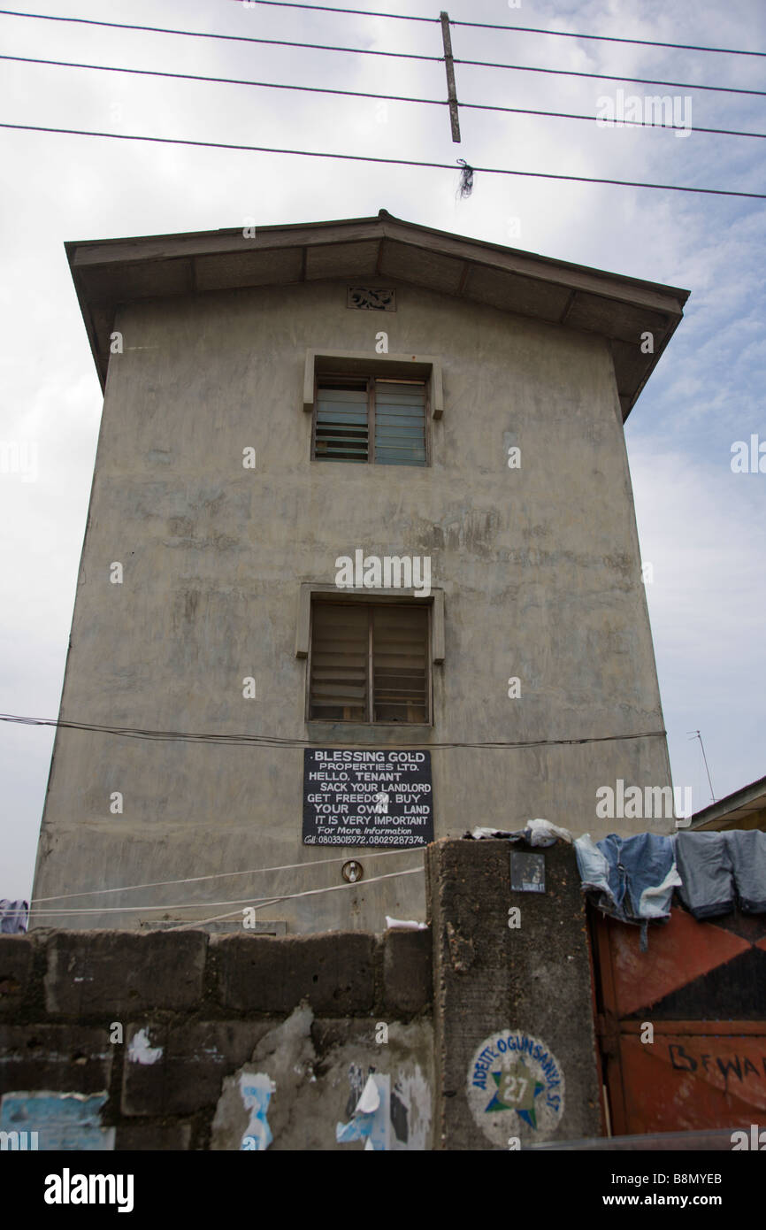 A sign advertises a building:  HELLO, TENANT SACK YOUR LANDLORD GET FREEDOM. BUY YOUR OWN LAND IT IS VERY IMPORTANT - Stock Image