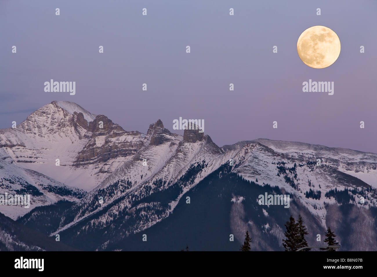 Full moon over the snow capped Fairholme Range at dusk during winter as viewed from 2nd Vermilion Lake near the - Stock Image