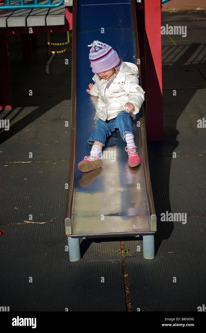 Little Girl in Winter Clothing Sliding Down Slide in Urban Playground - Stock Image