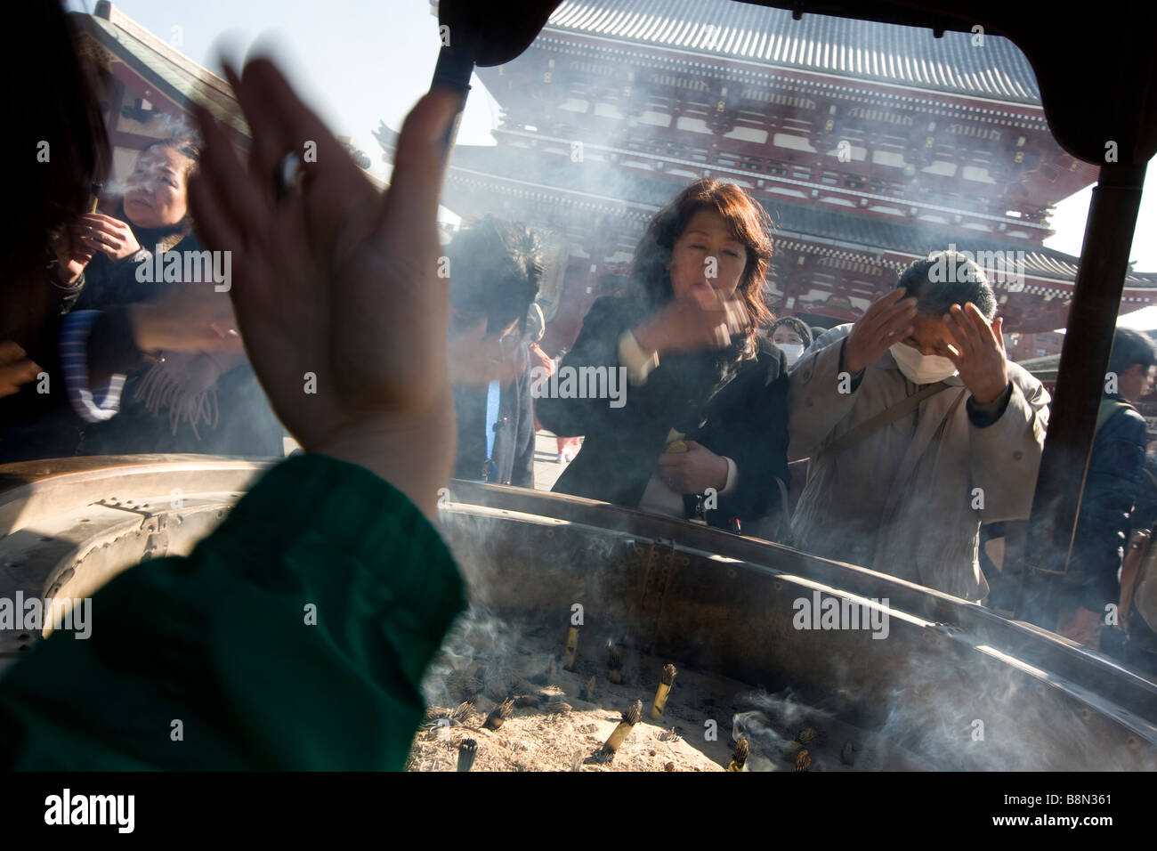 Visitors to Senso ji temple wave incense smoke over themselves from an urn to ward off poor health and to fix and Stock Photo