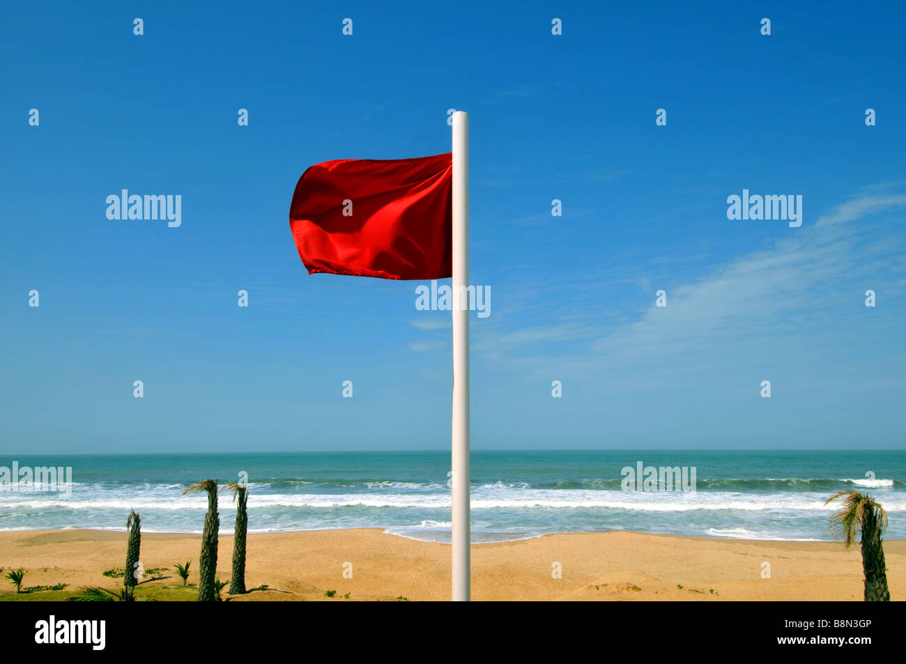 Red flag flying at a beach warning not to enter the water, The Gambia, West Africa - Stock Image