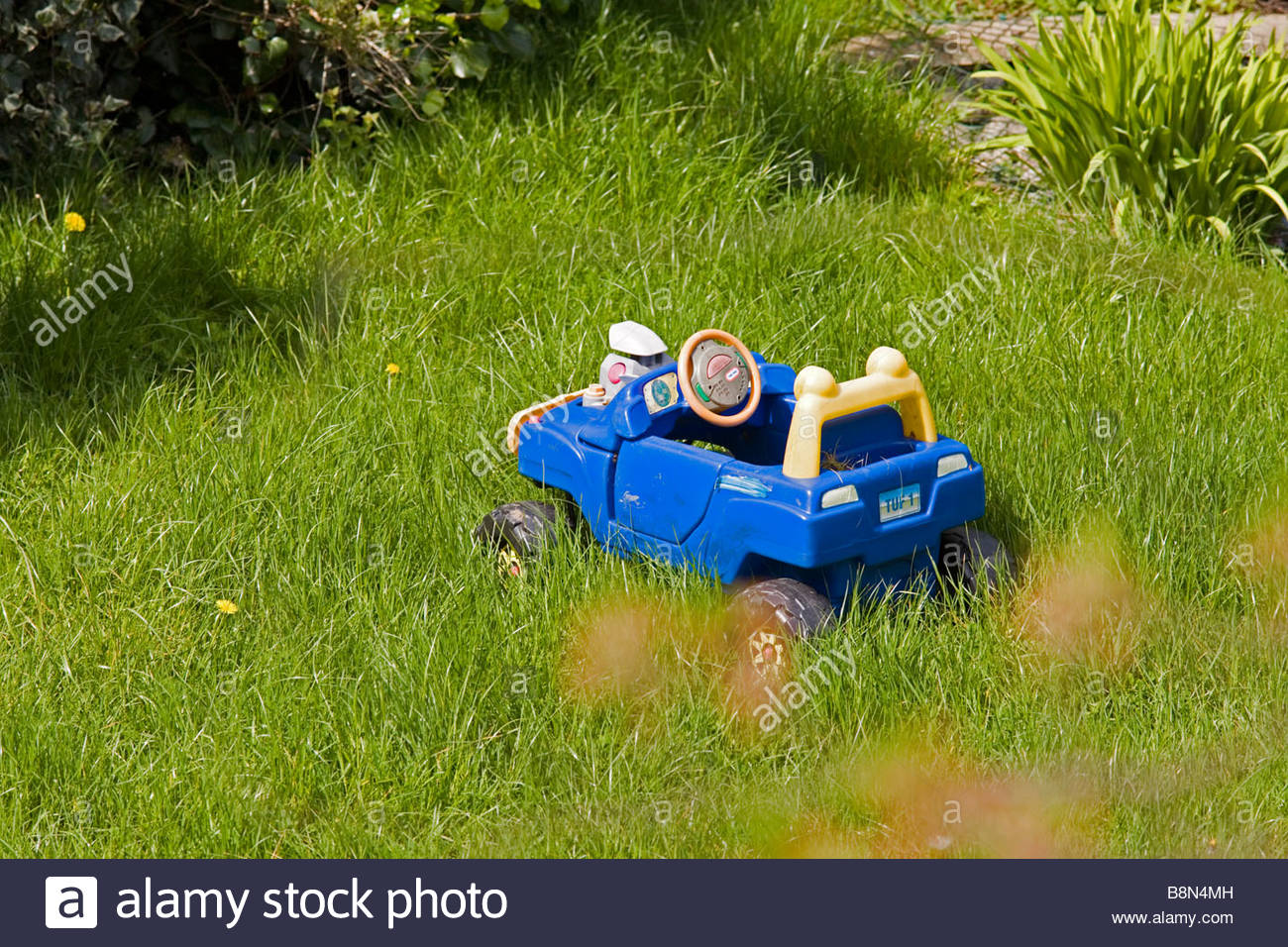 Childs plastic car left out in the garden amid long grass in a garden in London - Stock Image