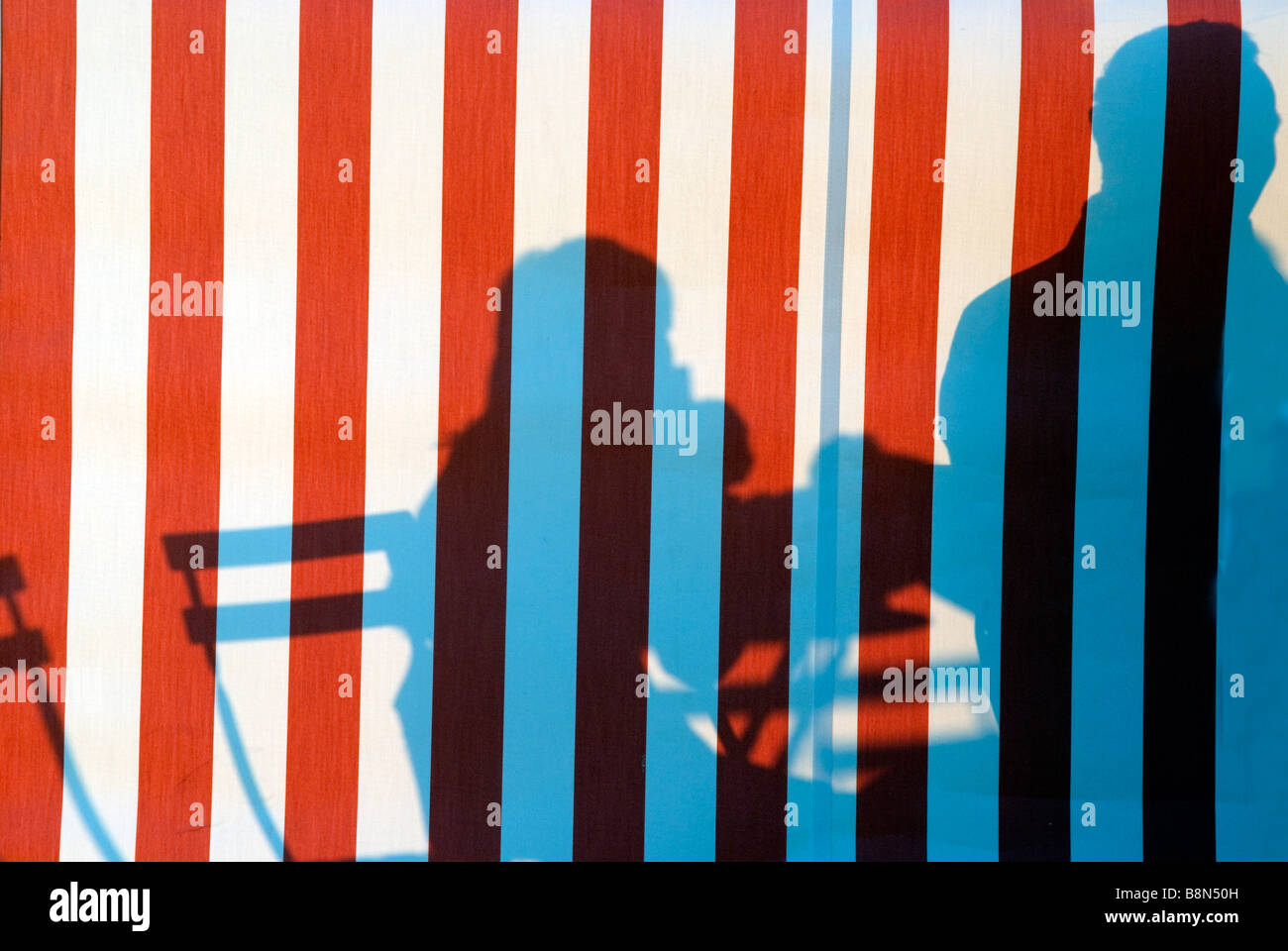 silhouettes of people at cafe projected onto red and white striped tent in sun - Stock Image
