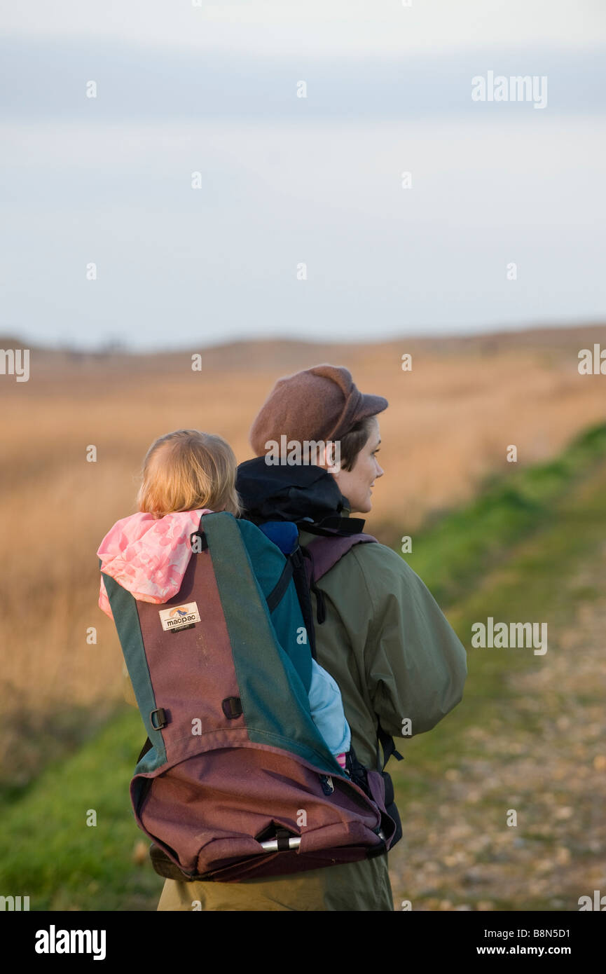 da9daaad00 mother carrying toddler in backpack along coastal path North Norfolk winter  - Stock Image