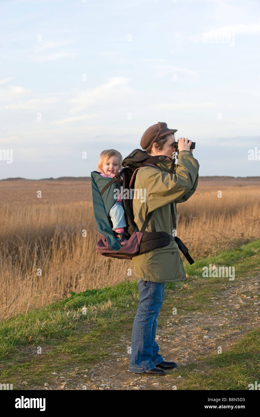 f7d821f564 mother carrying toddler in backpack while bird watching along coastal path  North Norfolk winter