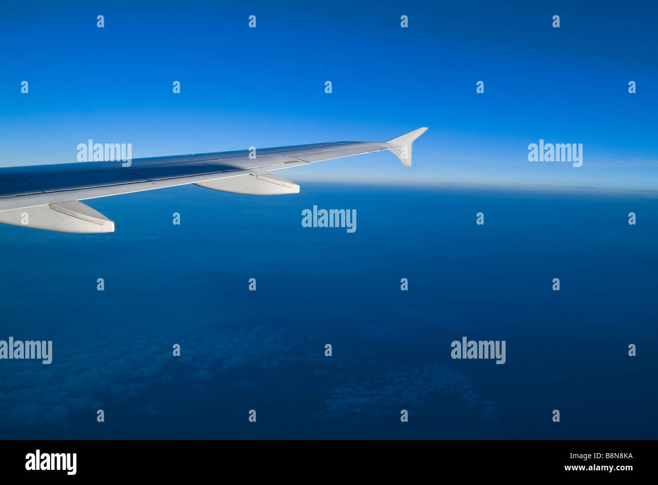 Airplane Wing With Blue Sky, Clouds & Horizon Stock Photo