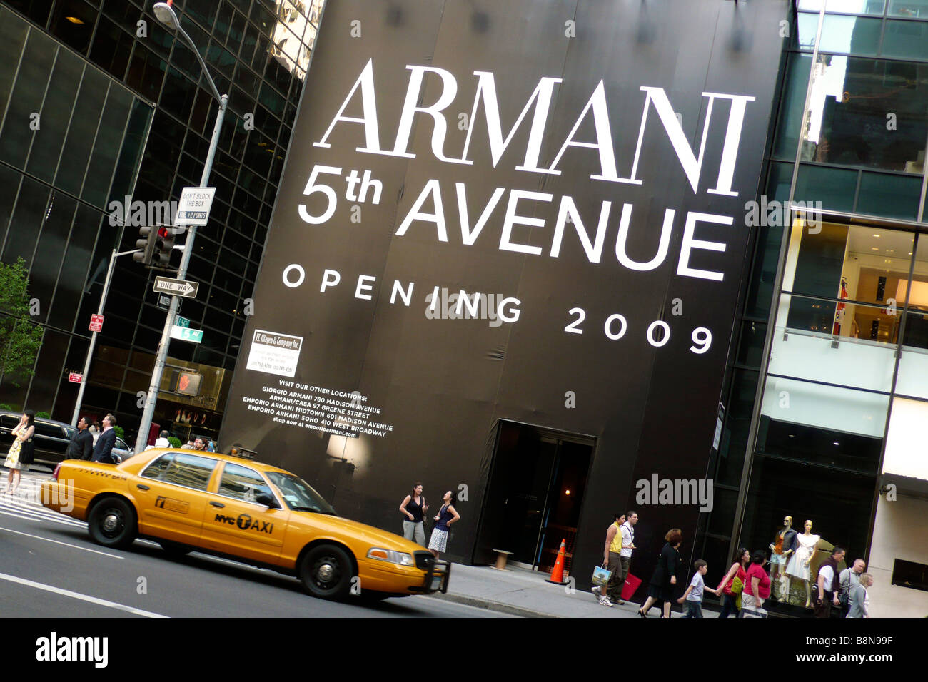 Yellow taxi cab outside the site of new Armani store on 5th avenue - Stock Image