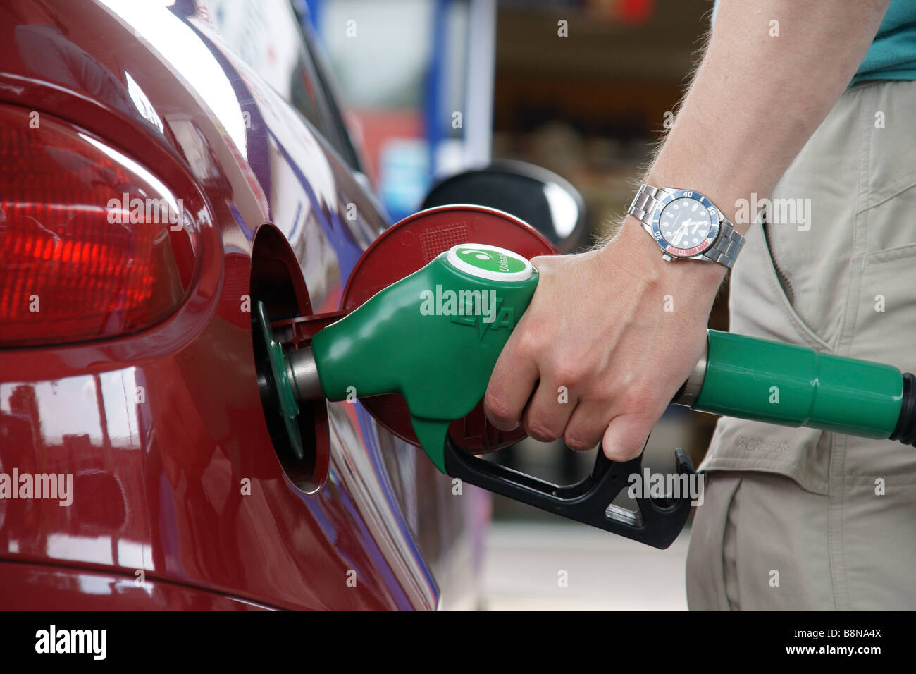 A man filling up his car with petrol at a self service station (c) Marc Jackson Photography - Stock Image