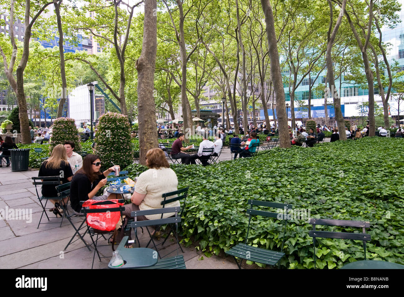 People sitting at small tables under tall trees in a public garden - Stock Image