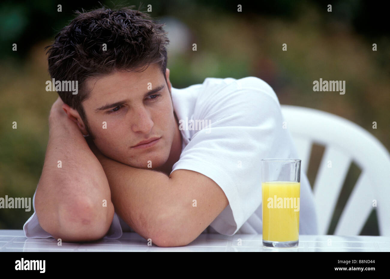 depressed man sitting outside with a glass of orange juice - Stock Image