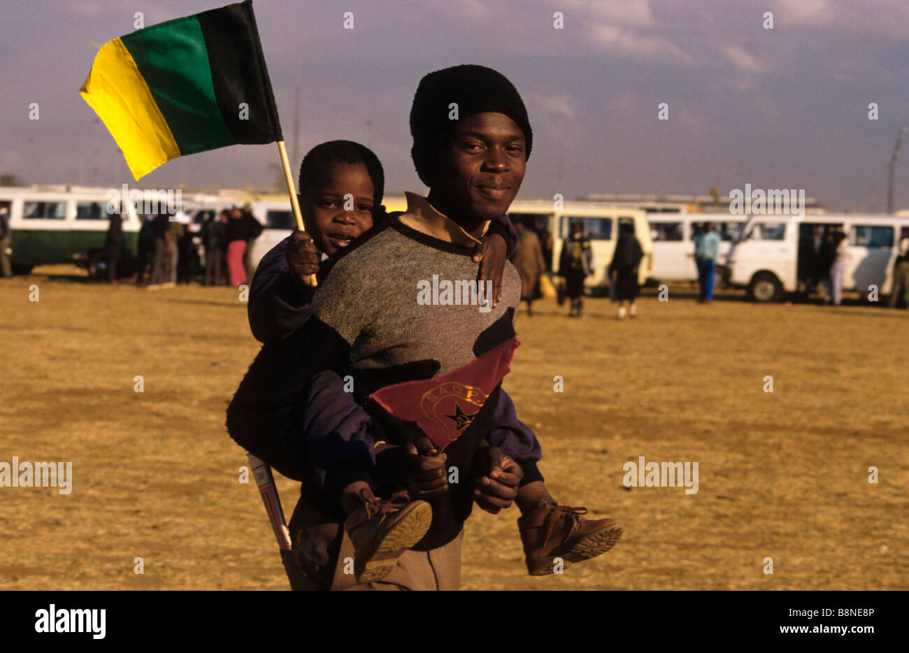 A man carries a child on his back waving the ANC flag at the Soweto launch of S.A.C.P (South African Communist Party) - Stock Image