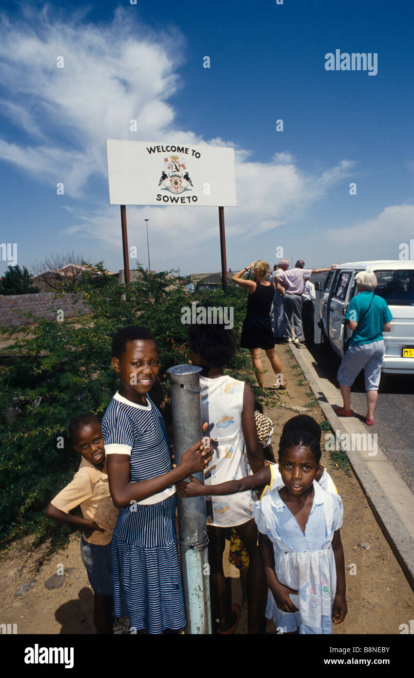 Tourists take pictures of a sign 'Welcome in Soweto' with a group of black children in the foreground looking on Stock Photo