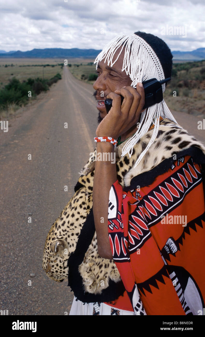 Chief Nicholas Gcaleka in traditional dress talking on a cell phone - Stock Image