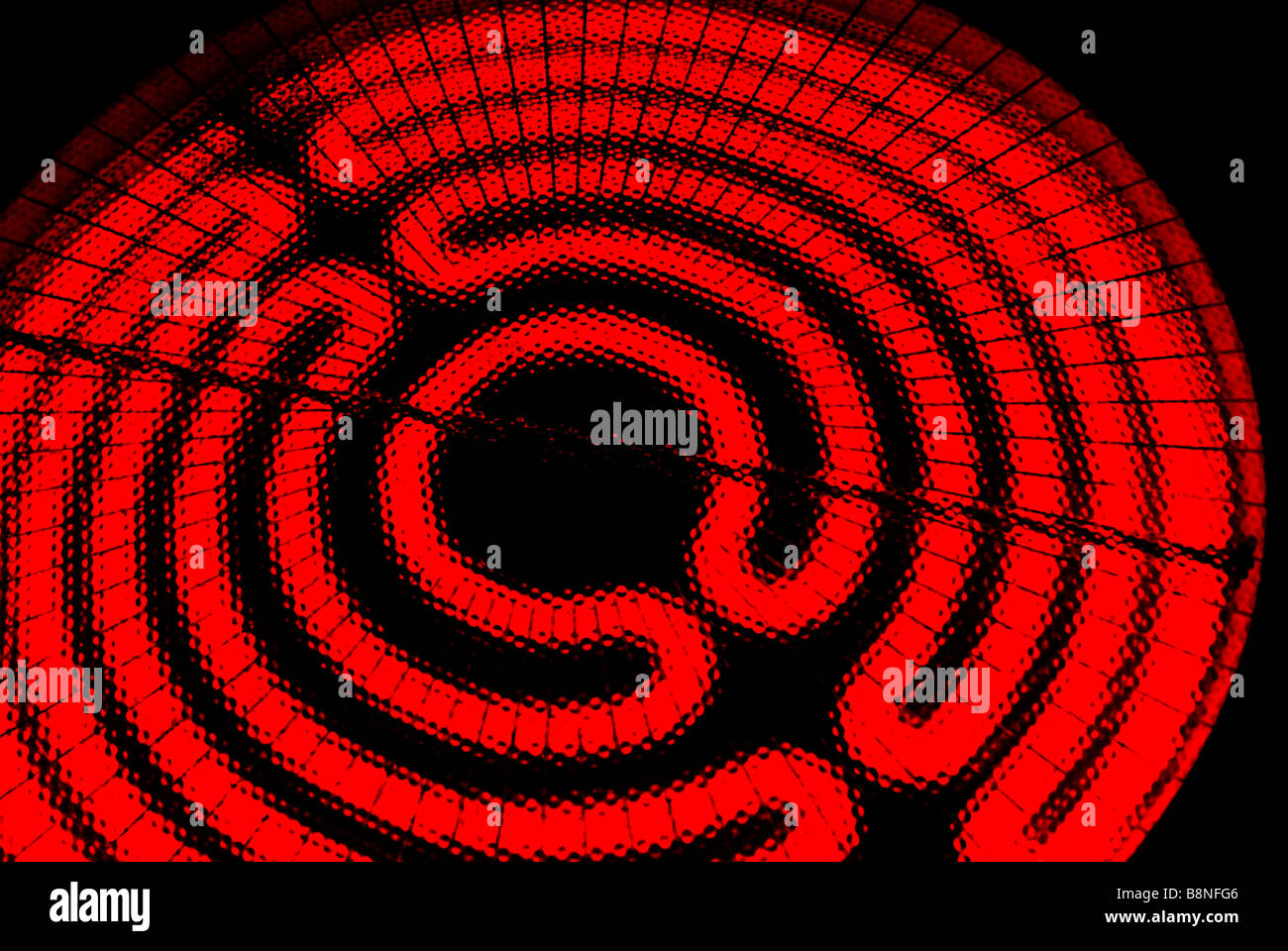 Glowing red, hot,  electric range cooktop burner heating element coil . - Stock Image