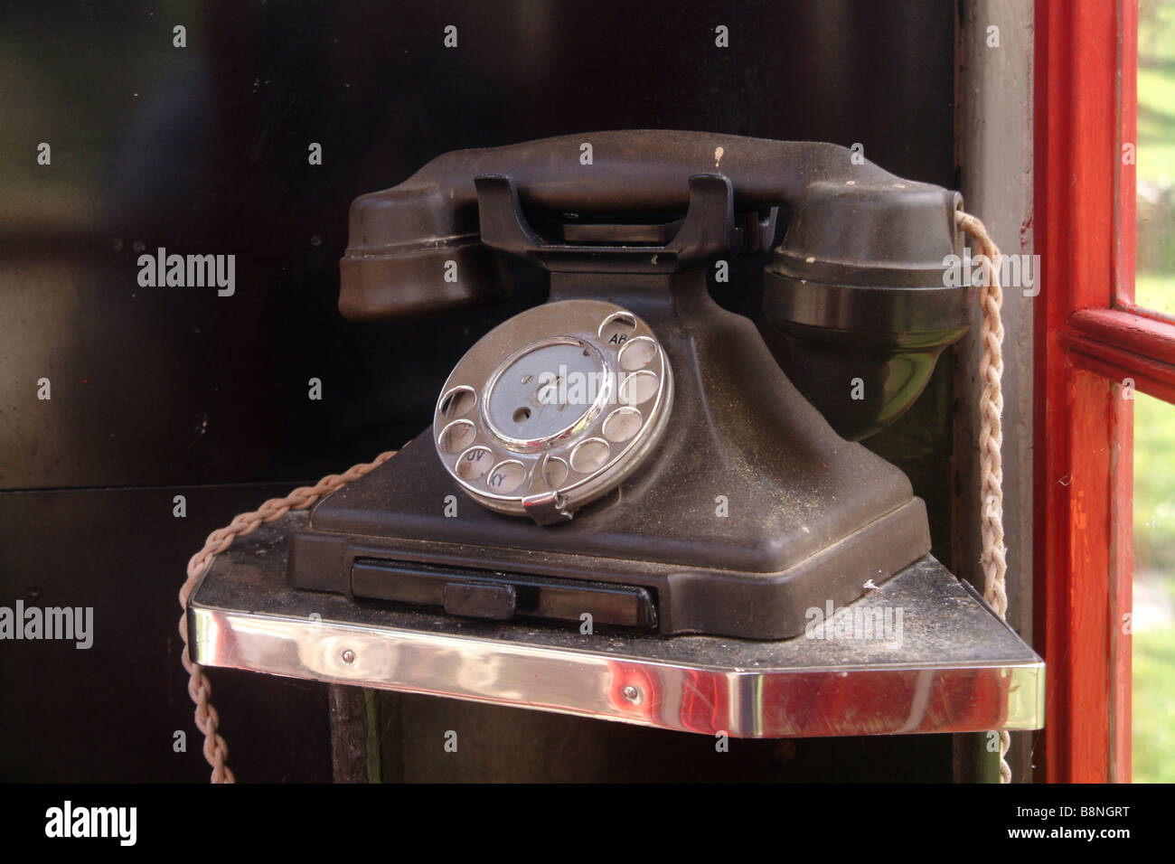 Original GPO 1/232 bakelite finger dial telephone with drawer in a 1940's public telephone box - Stock Image