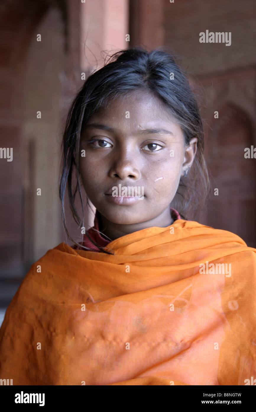 Young indian girl dressed in orange Sari inside a temple - Stock Image