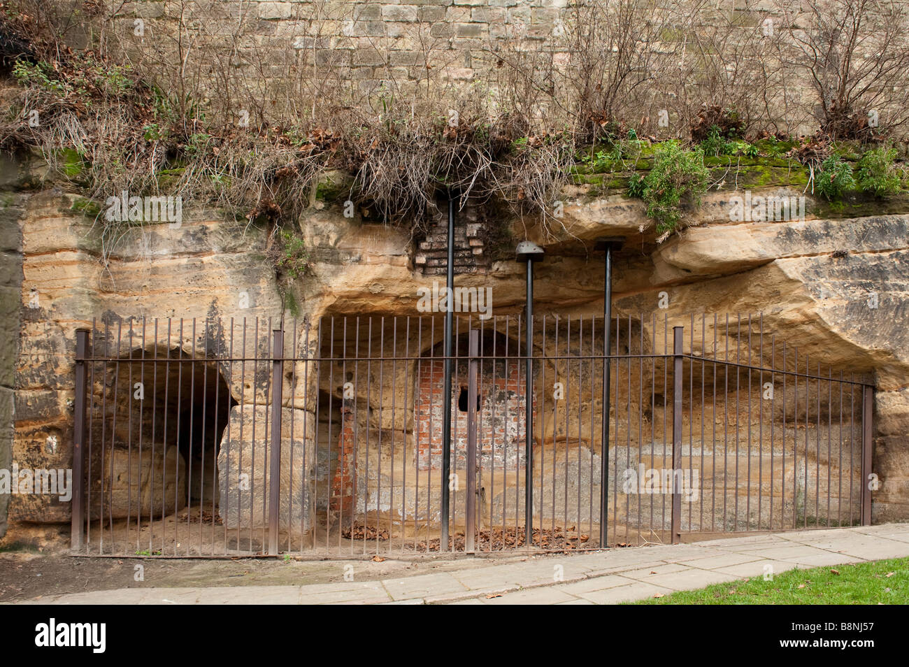 Three metal support props holding up a rock face underneath Nottingham Castle,England,'Great Britain' - Stock Image