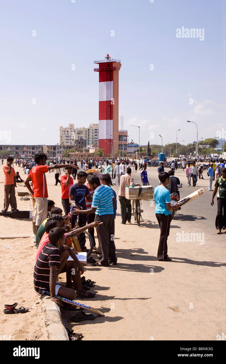 India Tamil Nadu Chennai beach multiple games of cricket played below the lighthouse - Stock Image