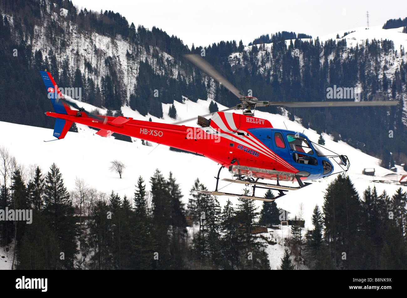 Chopper HB XSO Eurocopter As 350 B2 Ecureuil of Air Glaciers in action in a narrow mountain valley, Switzerland - Stock Image