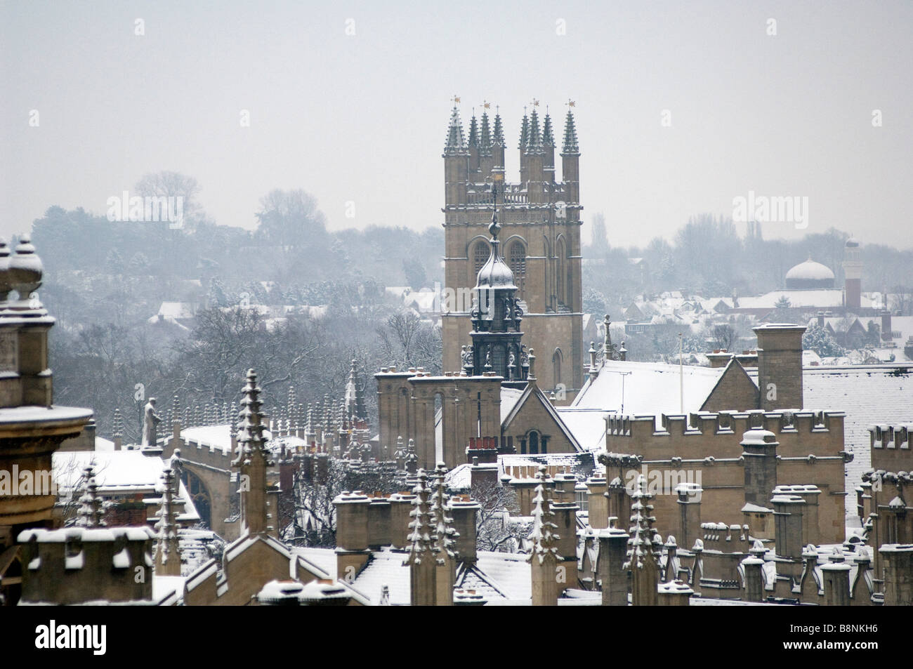 Looking across the rooves of Oxford Colleges towards Magdalen College Tower in snow and winter - Stock Image
