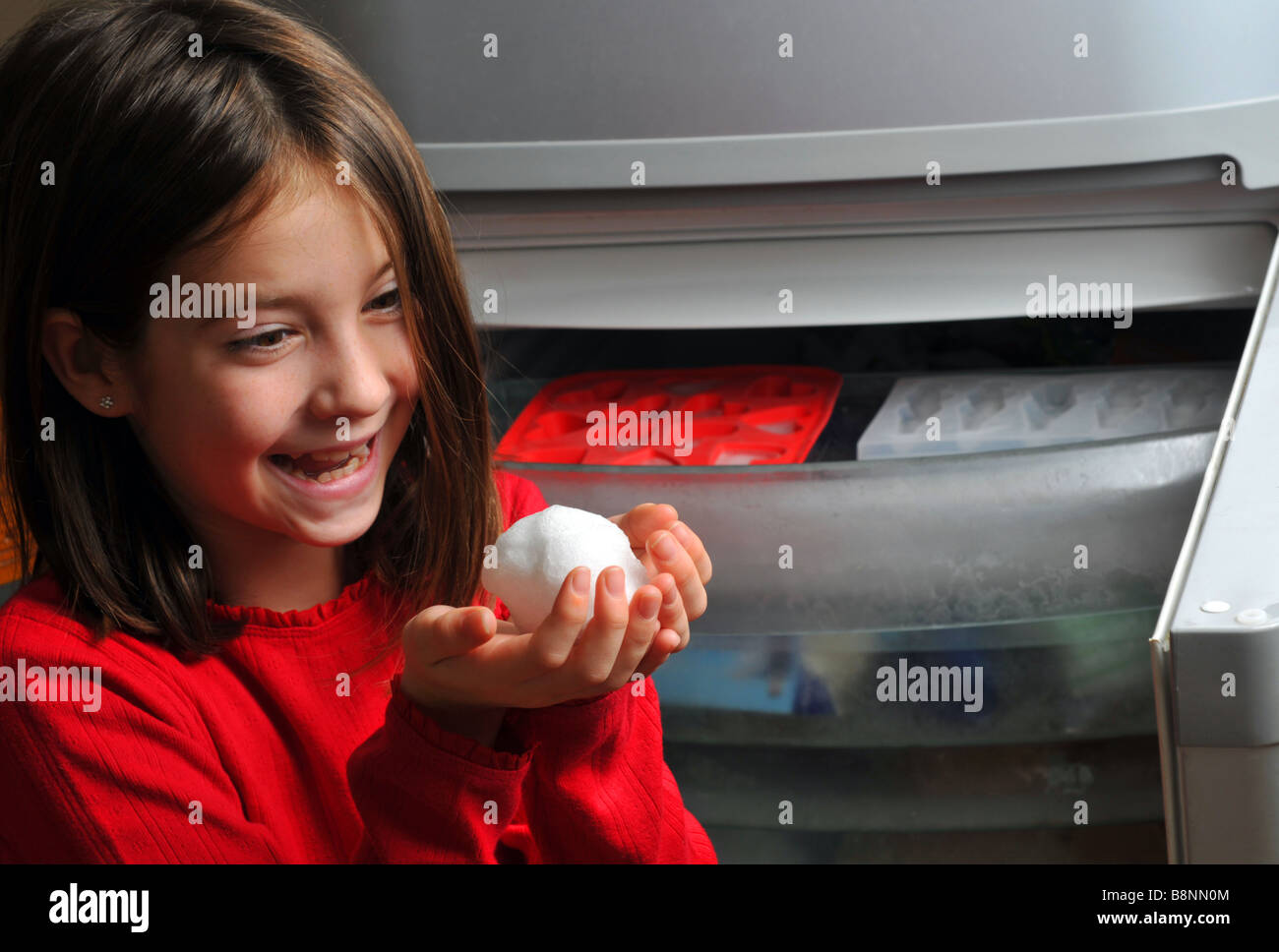 Girl keeps a snowball in the freezer - Stock Image