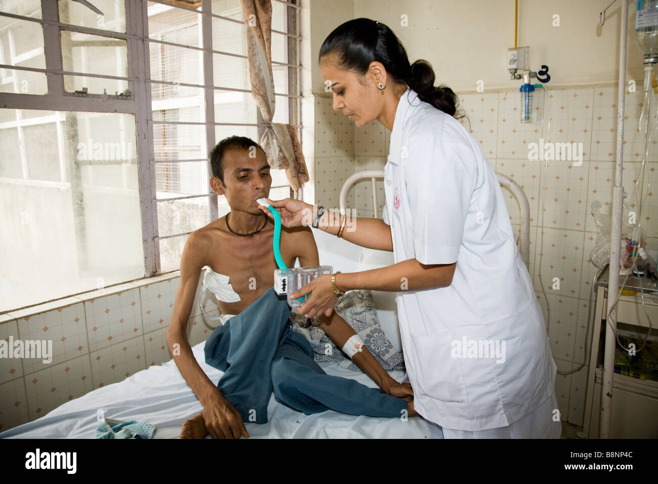 Nurse giving a breathing test to a sick patient on a general ward of the New Civil Hospital, Surat. Gujarat. India. - Stock Image