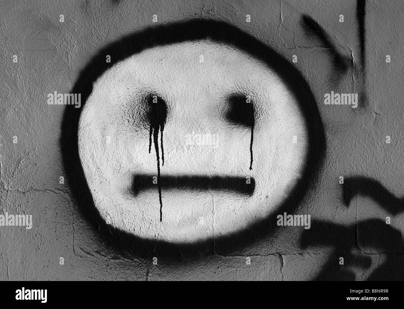 Graffiti smiley happy face on cement wall vandalism menacing eyes look like they are bleeding urban decay ghetto slum crime