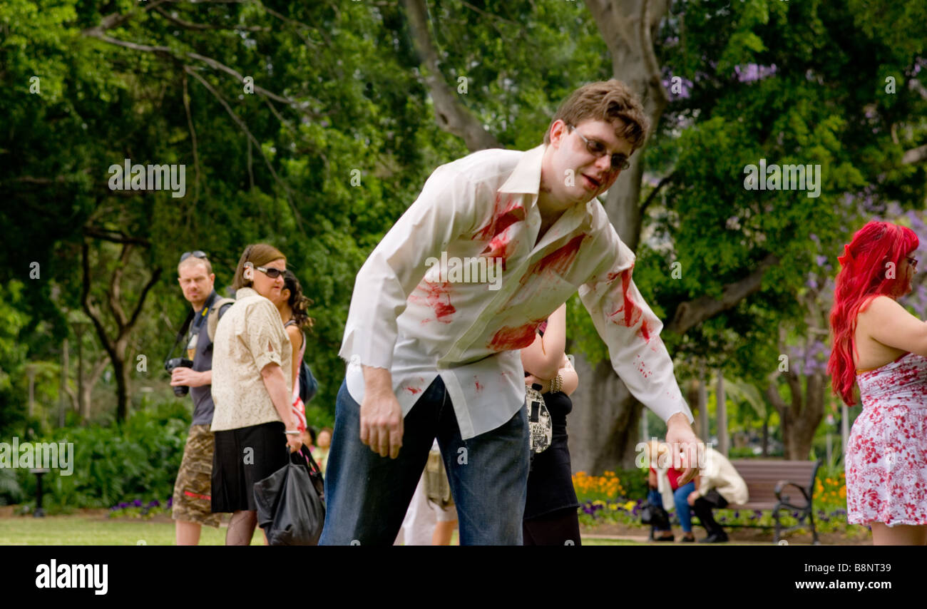Staggering zombie in Hyde Park is watched by onlookers. - Stock Image