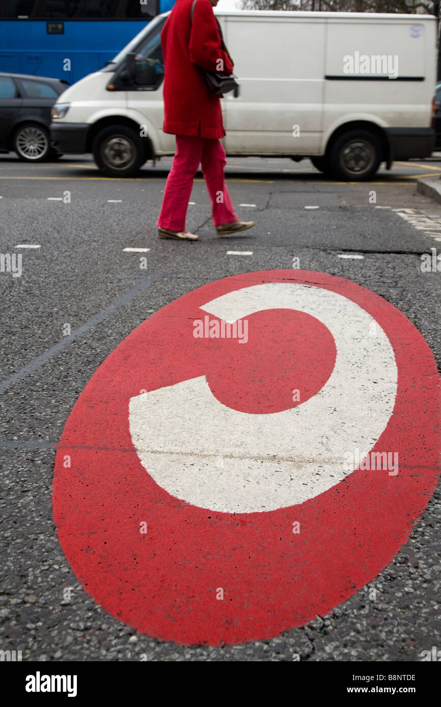 Congestion charging for London zone sign, and a pedestrian crossing the road, on the A4 road in West London. - Stock Image