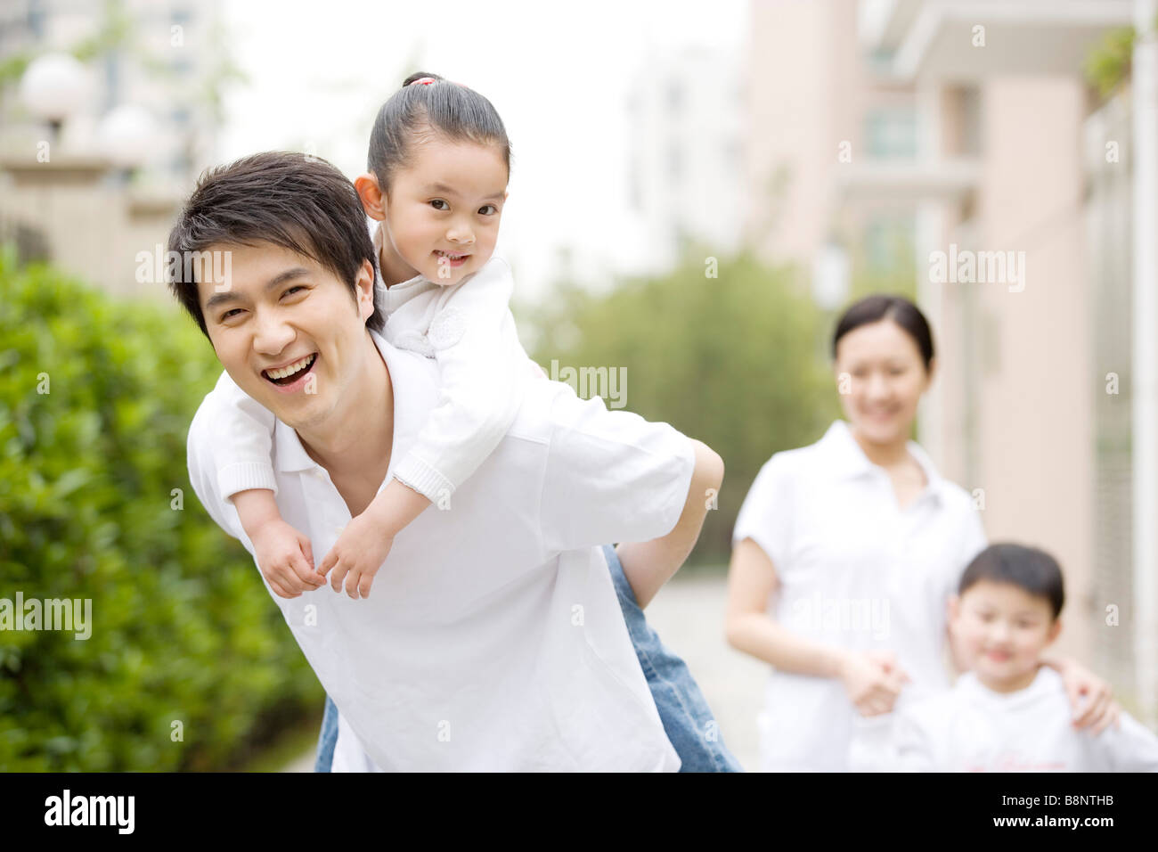 Father giving daughter piggyback mother and son in background - Stock Image
