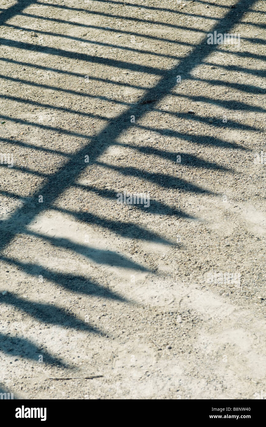 Shadow of wrought iron fence on gravel - Stock Image