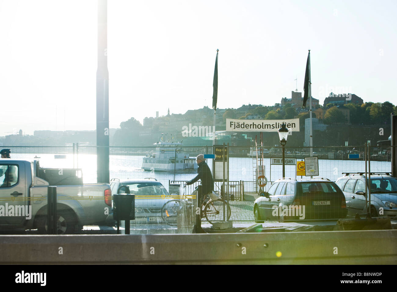 Sweden, Stockholm, busy street with canal and ferry in background - Stock Image