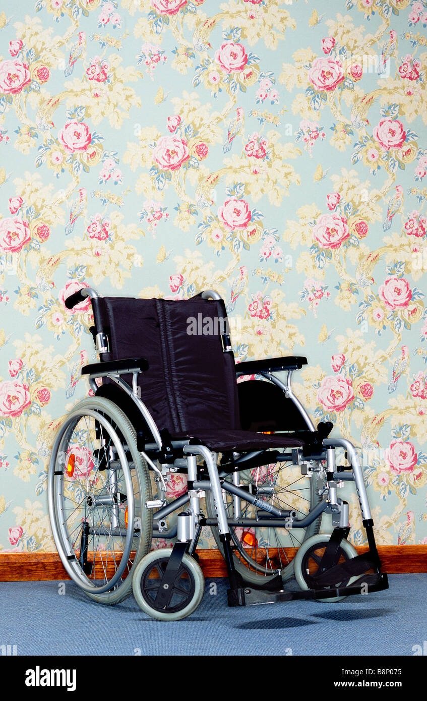 wheelchair against floral wall paper - Stock Image
