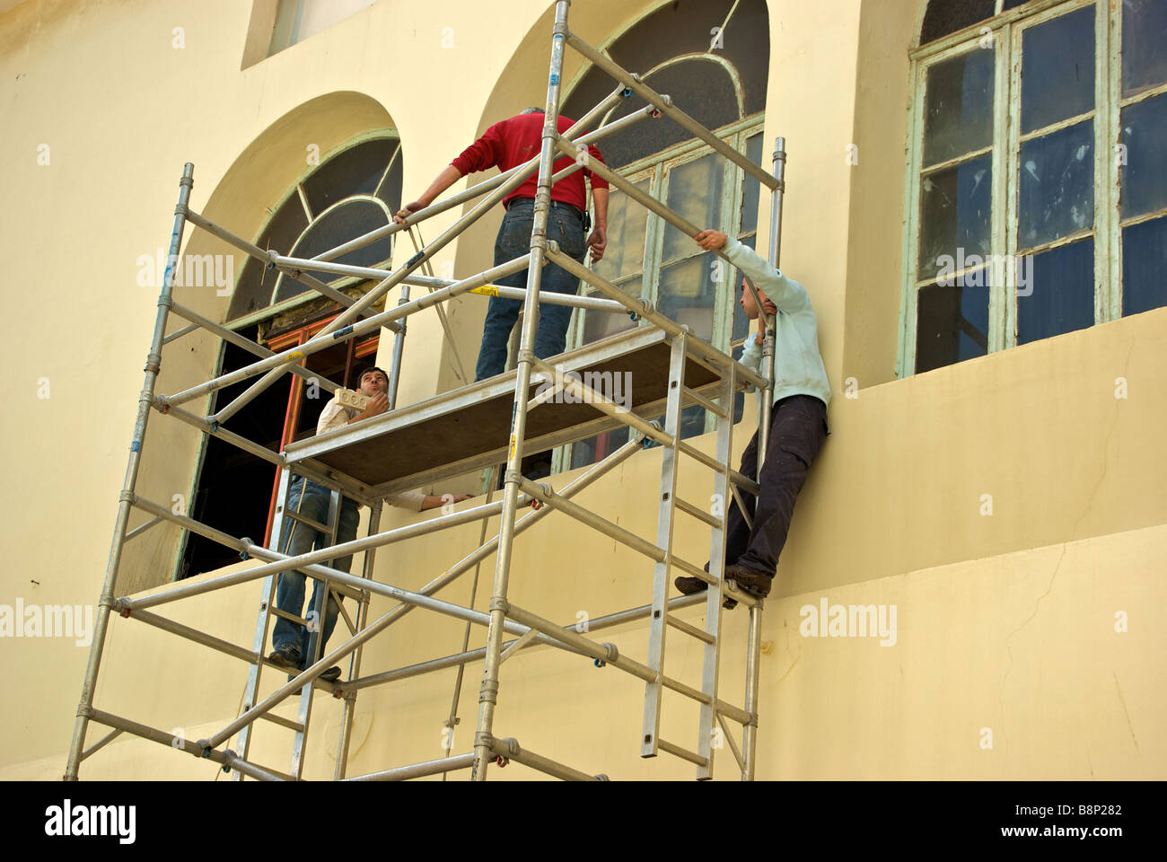 Three workmen on scaffold repairing windows of first Hebrew Language school in Neve Tzedek Neighbourhood neighborhood Stock Photo